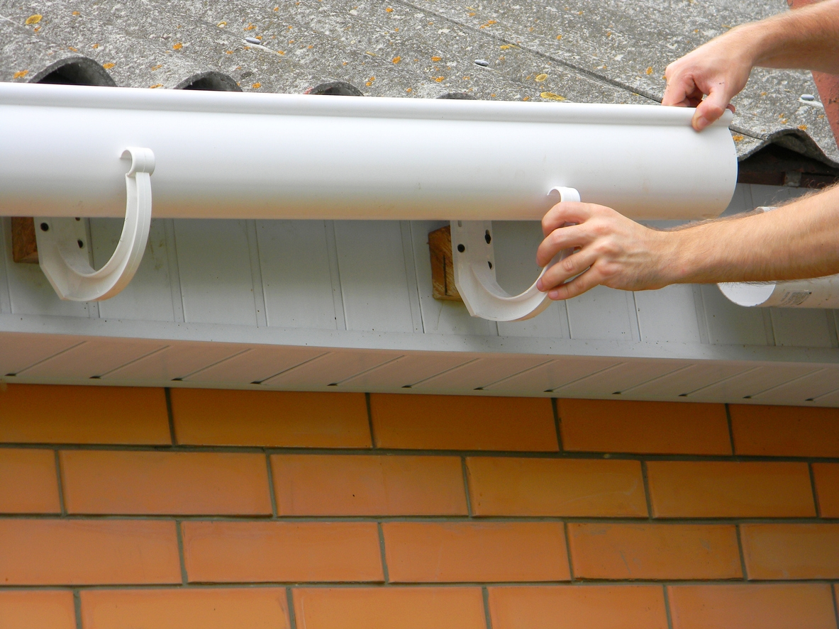 Contractor installing plastic roof gutter. Plastic Guttering  Replace, Rain Guttering & Drainage Repair by Handyman hands.